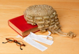 Barristers wig on legal book beside spectacles
